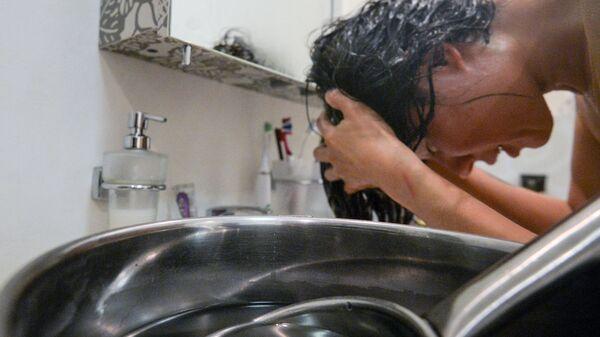Девушка моет голову нагретой водой во время сезонного отключения горячей воды в Москве. Архивное фото