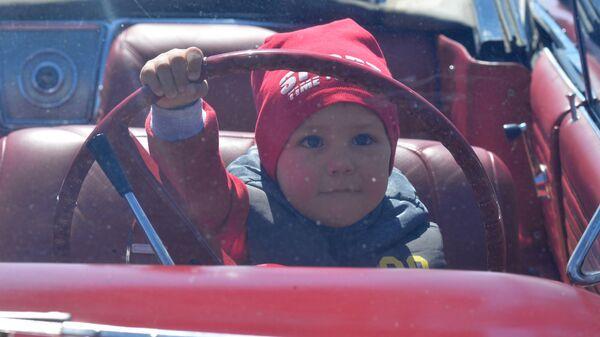 Ребенок за рулем автомобиля на международном фестивале Ретро-Минск-2017 на площади Государственного флага в Минске