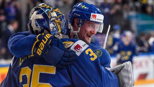 Вратарь сборной Швеции Хенрик Лундквист и игрок сборной Швеции Антон Строльман радуются победе в матче между сборными командами Швейцарии и Швеции