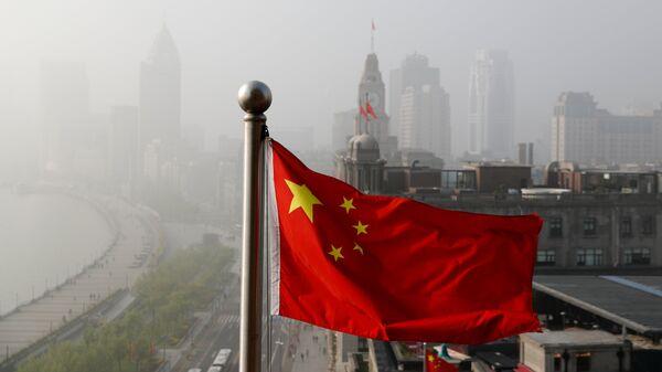 Флаг Китая развевается над офисными зданиями в Шанхае