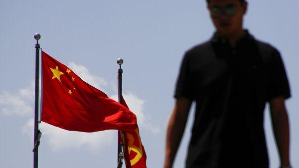 Мужчина рядом с национальным флагом Китая и флагом банка Китая в Пекине