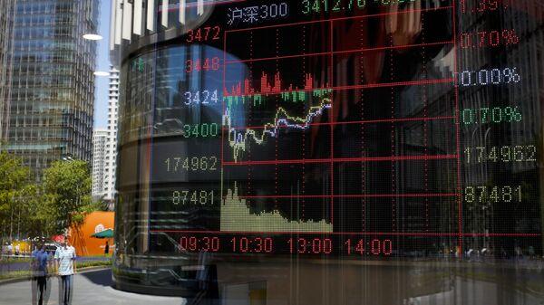 Биржевые графики отражаются в стекле брокерской фирмы в Пекине