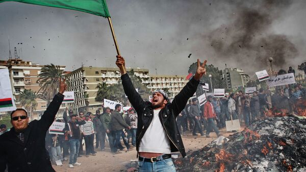 Жители Бенгази сжигают портреты Муамара Каддафи, плакаты с его цитатами и Зеленую книгу Каддафи