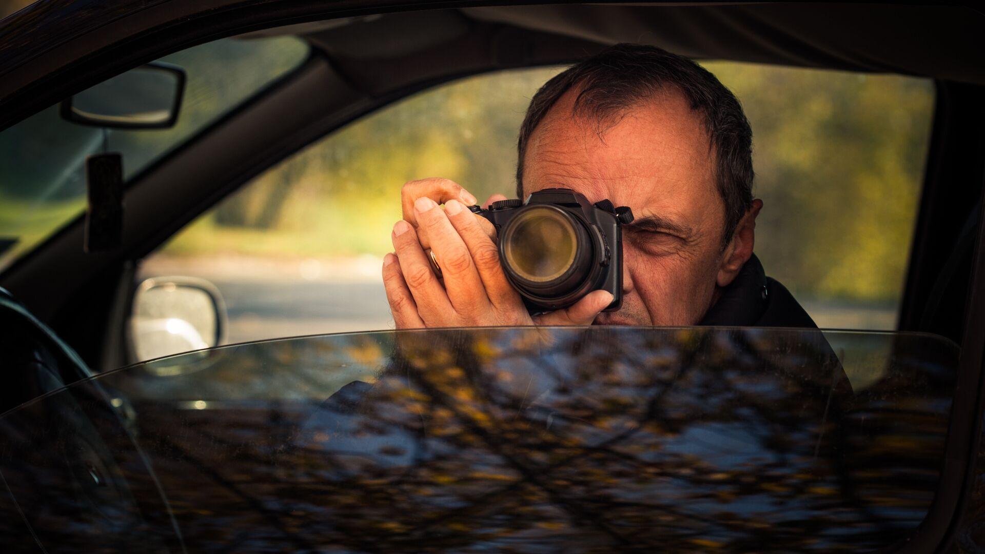 Мужчина фотографирует из окна автомобиля  - РИА Новости, 1920, 06.10.2021