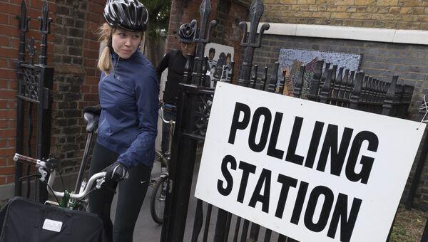 Девушка выходит с избирательного участка в Лондоне