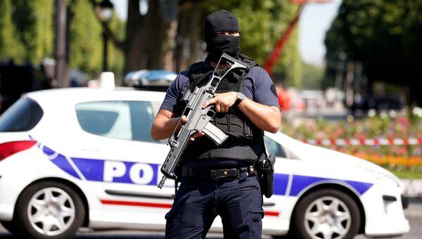 Полицейский в районе Елисейских полях в Париже. Архивное фото
