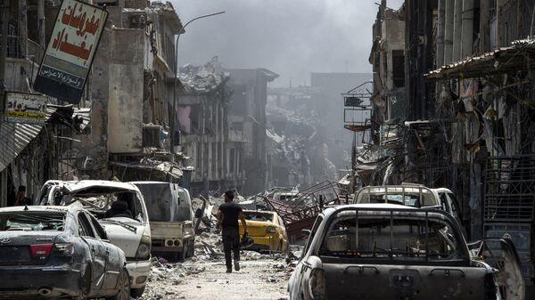 Мужчина идет вдоль сгоревших автомобилей в Мосуле. Архивное фото