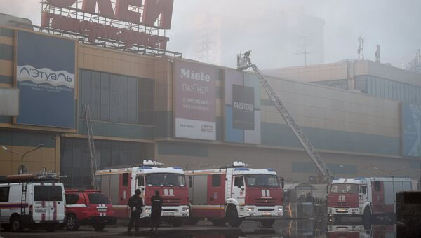 Сотрудники полиции и противопожарной службы во время тушения пожара в здании торгового центра РИО на Дмитровском шоссе в Москве
