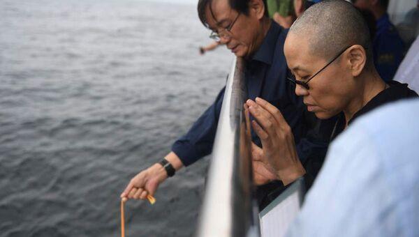 Лю Ся, вдова китайского правозащитника Лю Сяобо, опускает урну с его прахом в море. 15 июля 2017