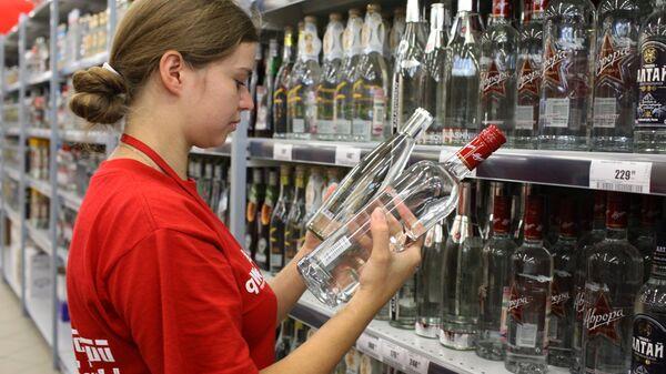 Работница супермаркета в алкогольном отделе. Архивное фото
