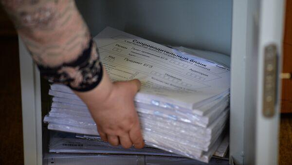 Сотрудник достает из сейфа пакеты с контрольно-измерительными заданиями перед началом ЕГЭ