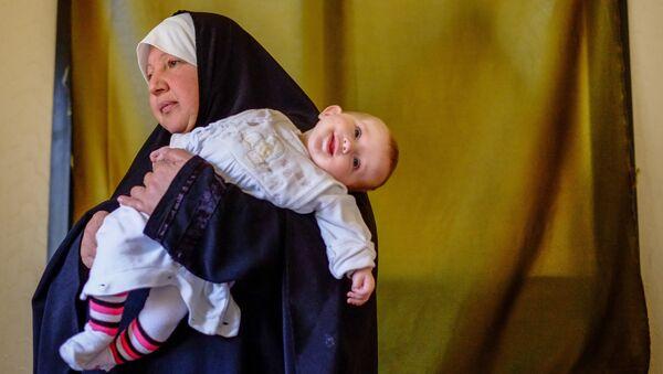 Женщина с ребенком — беженцы из Сирии — в одном из домов в городе Хальба на севере Ливана