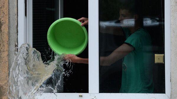 Юноша вычерпывает воду из своей квартиры на затопленной улице Уссурийска. 7 августа 2017