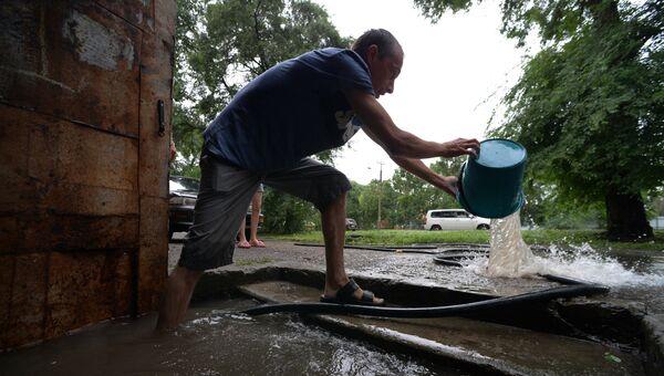 Мужчина вычерпывает воду из подъезда на затопленной улице Уссурийска. 7 августа 2017