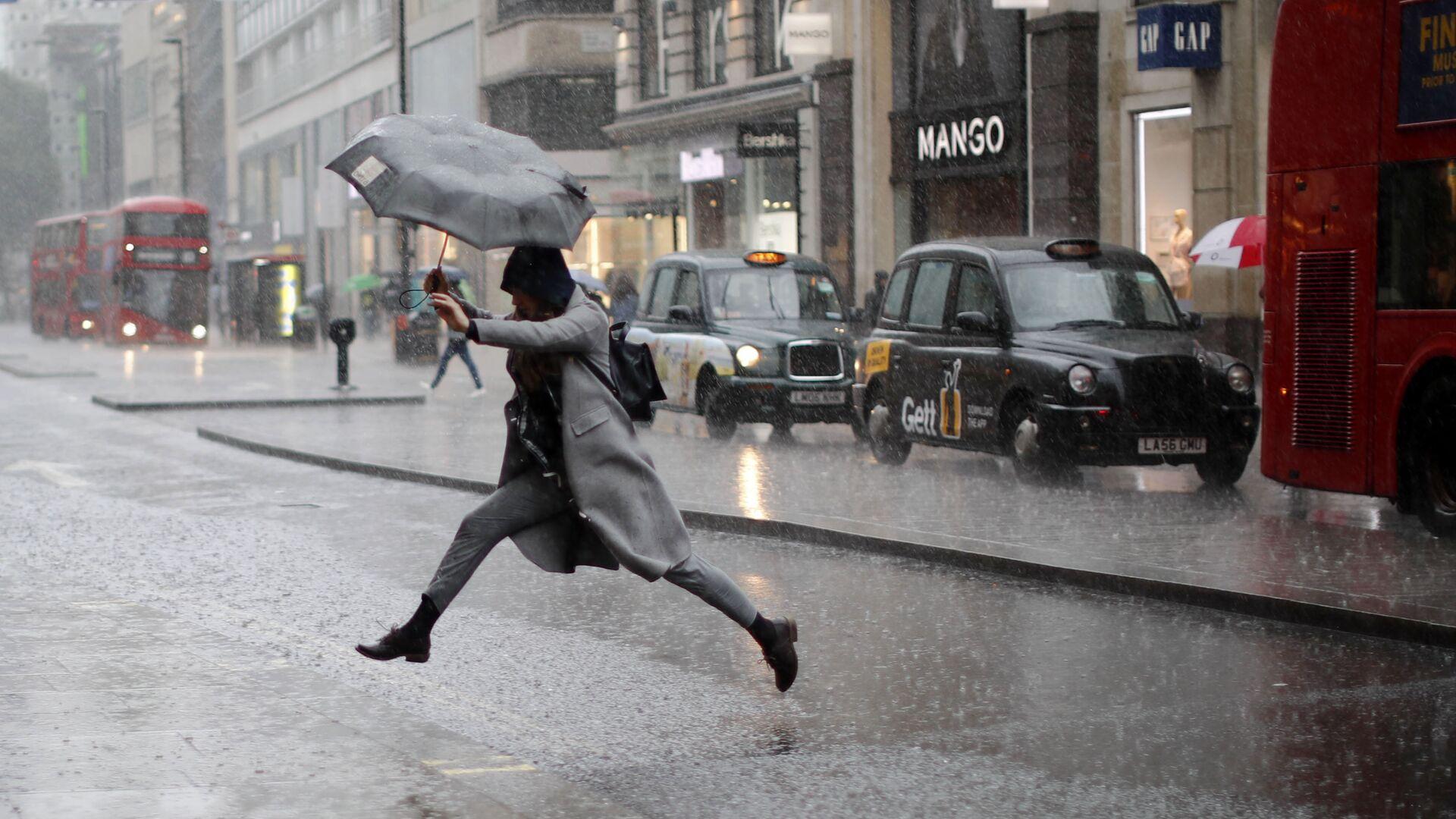 Девушка перепрыгивает лужу во время дождя в Лондоне. 9 августа 2017 - РИА Новости, 1920, 26.07.2021
