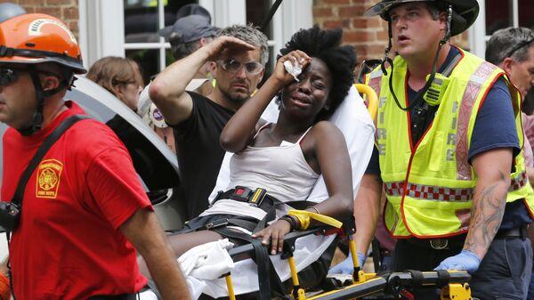 Спасатели оказывают женщине первую помощь после того, как автомобиль наехал на участников протестов в Шарлоттсвилле, штат Вирджиния