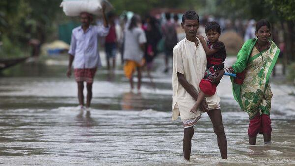 Люди во время наводнения в деревне Мурката к востоку от Гаухати в Индии