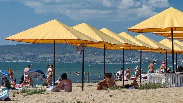 Отдыхающие на пляже на берегу Черного моря в поселке Береговое