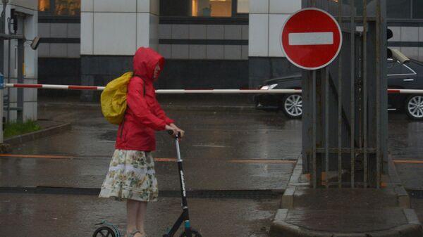 Девушка на самокате во время дождя в Москве