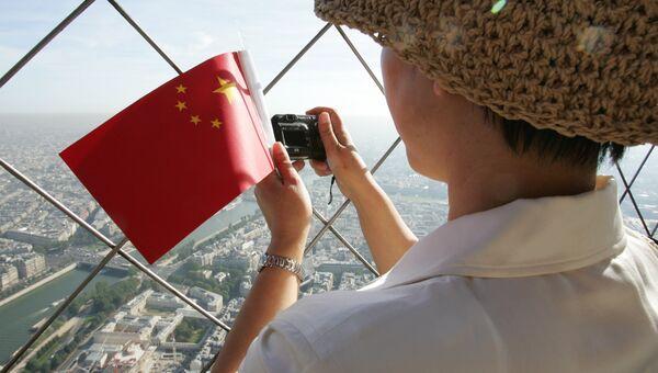Китайский турист на смотровой площадке Эйфелевой башни во Париже