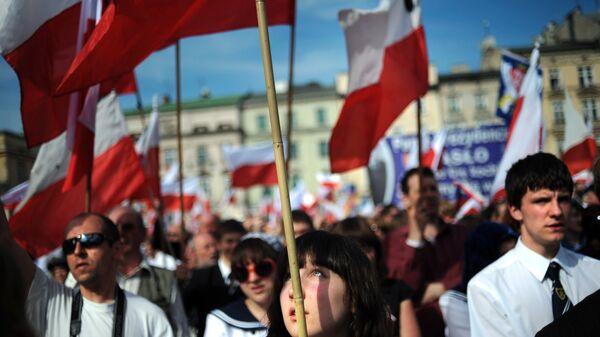 Жители Кракова с польскими флагами на площади города