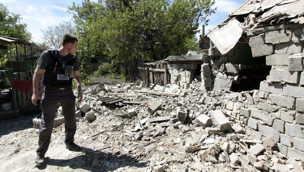 Сотрудник ОБСЕ осматривает двор жилого дома, пострадавший в результате обстрела в Донецкой области. Архивное фото