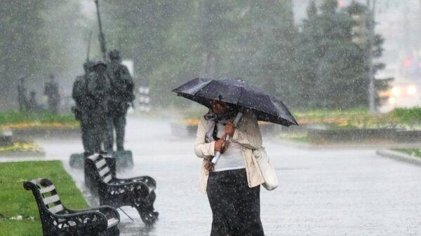 Женщина идет по Фрунзенской набережной в Москве во время дождя. Архивное фото