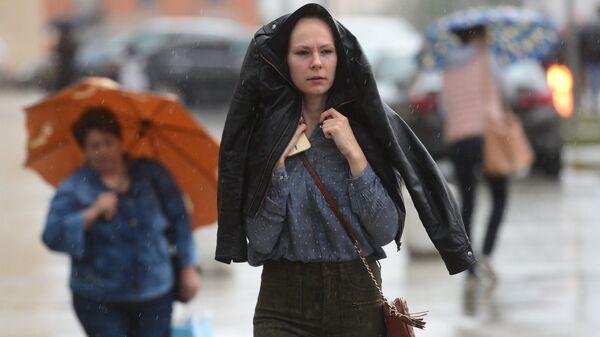 Прохожие идут на Смоленской площади во время дождя в Москве