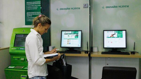 Сотрудница дополнительного офиса Сбербанка в зале обслуживания физических и юридических лиц