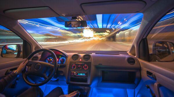 Мужчина за рулем автомобиля ночью