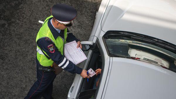 Сотрудник ГИБДД проверяет документы. Архивное фото