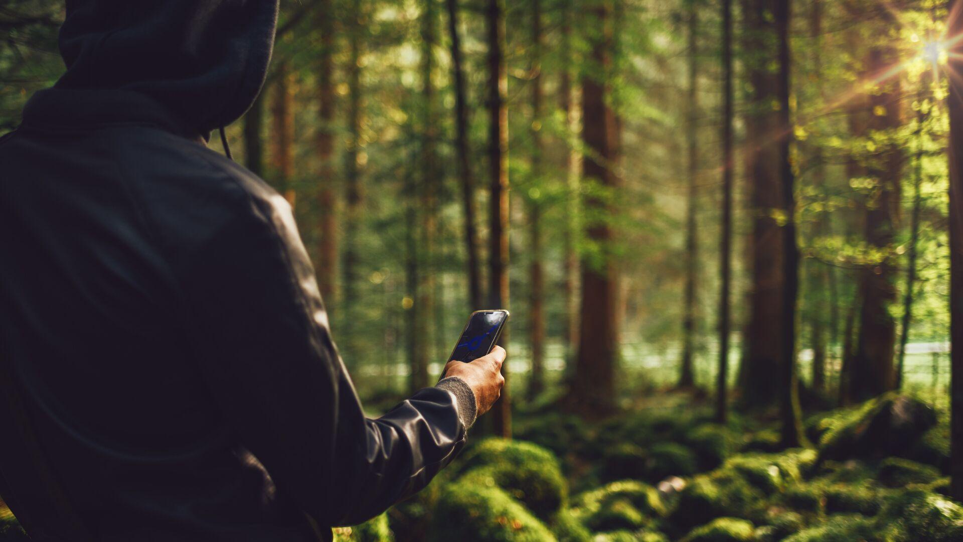 Молодой человек в лесу с телефоном - РИА Новости, 1920, 10.09.2021
