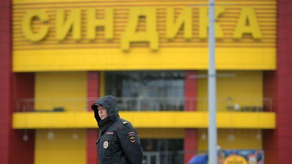 Сотрудник полиции на месте ликвидации последствий пожара на строительном рынке Синдика