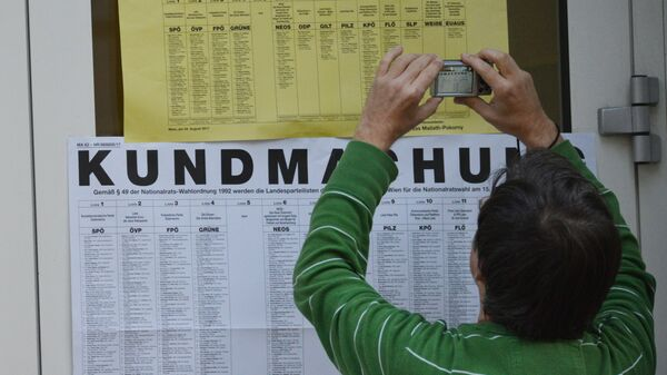 Житель Вены фотографирует у входа на избирательный участок списки партий, участвующих в парламентских выборах в Австрии. 15 октября 2017
