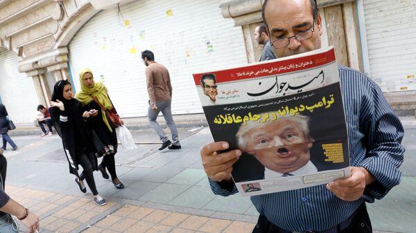 Мужчина читает ежедневную газету на улице Тегерана после заявления президента США Дональда Трампа о политике США относительно Ирана