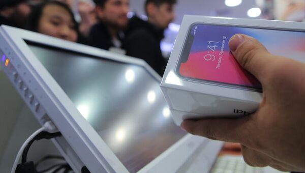 Продавцы за прилавком во время старта продаж нового смартфона iPhone X в магазине Связной на Тверской улице в Москве.