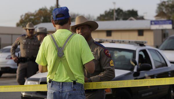 Мужчина разговаривает с сотрудником правоохранительных органов США на месте стрельбы у церкви в Сазерленд-Спрингс в Техасе, США. 5 ноября 2017