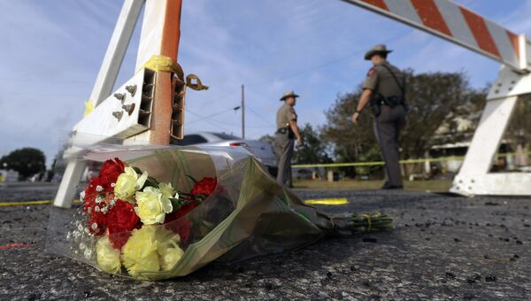 Цветы у блокпоста, где сотрудники правоохранительных органов работают на месте стрельбы у церкви в Сазерленд-Спрингс в Техасе, США. Архивное фото