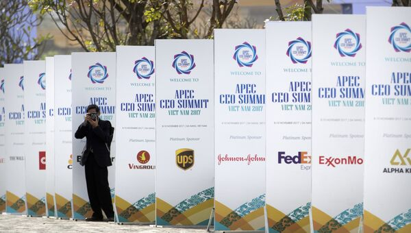 Фотограф на фоне баннеров саммита АТЭС в Дананг, Вьетнам
