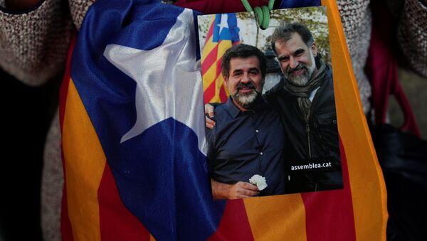 Женщина с фотографией Жорди Санчеса и Жорди Куишара во время митинга в Барселоне. 27 октября 2017