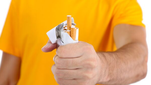 Мужчина сжимает пачку сигарет