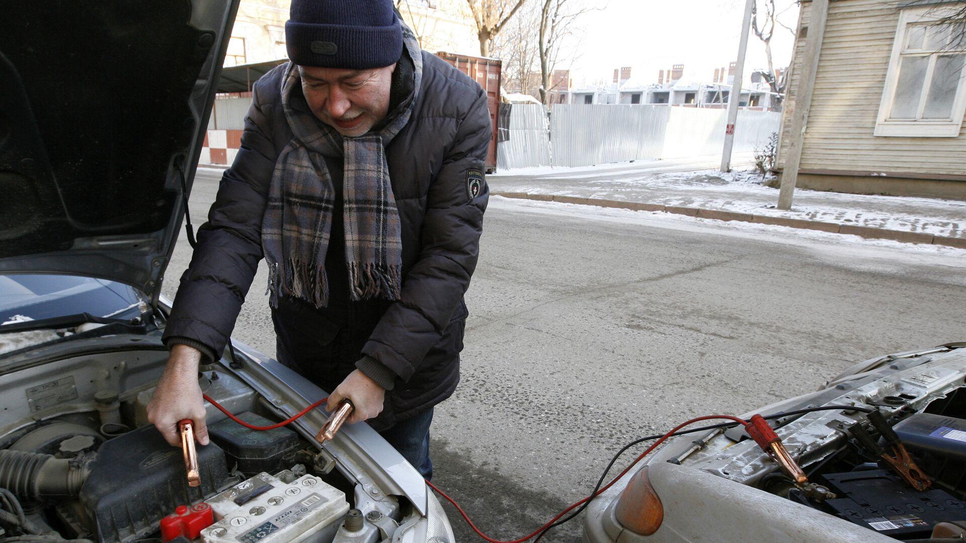 Мужчина прикуривает аккумулятор от другого автомобиля - РИА Новости, 1920, 09.02.2021
