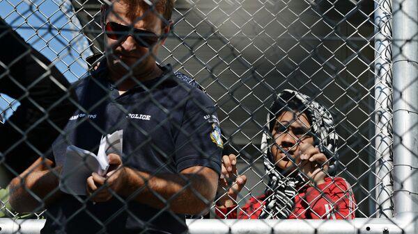 Полицейский в лагере беженцев в Греции. Архивное фото