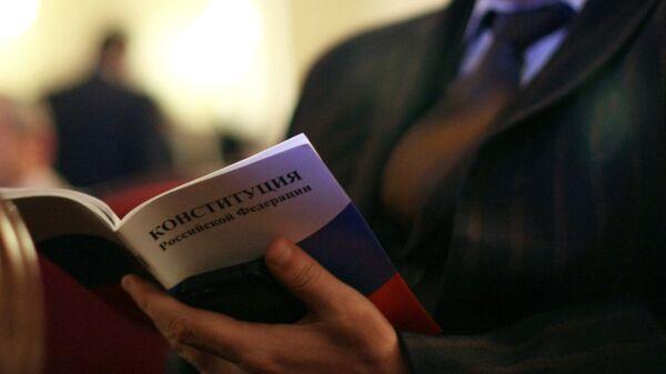 Мужчина с Конституцией РФ в руках на торжественном мероприятии, посвященном Дню Конституции РФ