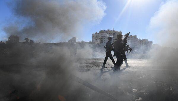 Сотрудники правоохранительных органов Израиля во время столкновений на границе Палестины и Израиля около Рамаллы. 9 декабря 2017