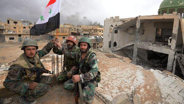 Солдаты сирийской армии (САА) с флагом Сирии. Архивное фото