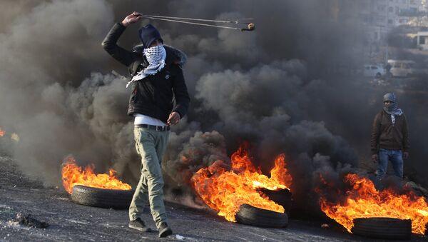 Протестующие во время столкновений на границе Палестины и Израиля в районе Рамаллы. 11 декабря 2017