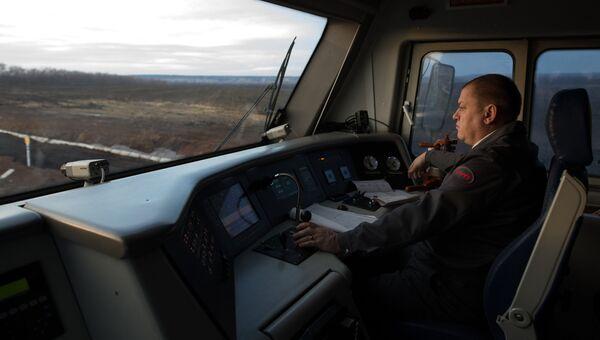 Машинист в кабине пассажирского поезда. Архивное фото