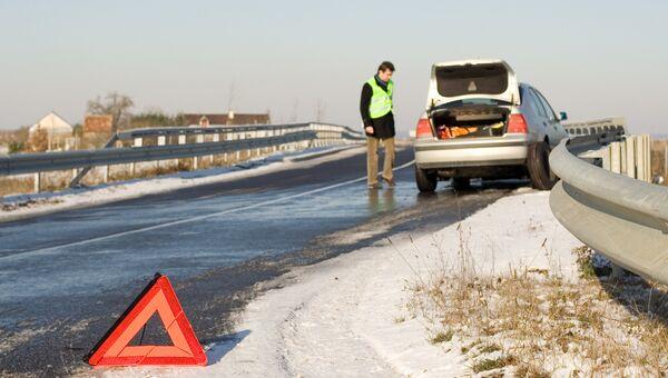Водитель в светоотражающем жилете у автомобиля