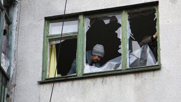 Женщина у окна жилого дома в центре города Ясиноватая, пострадавшего в результате обстрела. 21 декабря 2017